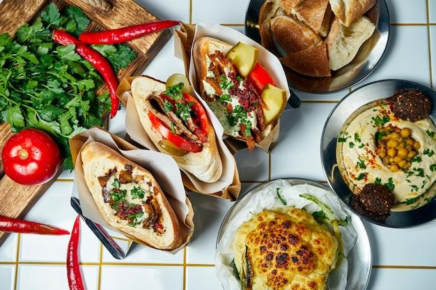 Vista superior no pão árabe delicioso do alimento da rua e no húmus na tabela branca. pão árabe saboroso com tomate, cebola e molho, hambúrguer de carne sobre uma mesa branca. cozinha grega.