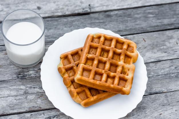 Vista superior no prato de waffles belgas ou vienenses com um copo de leite fresco na mesa de madeira rústica. Foto Premium