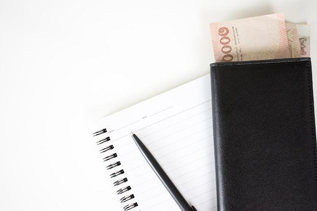 Vista superior note book com caneta e dinheiro no bolso em uma mesa branca com espaço de cópia.