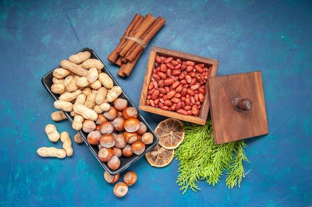 Vista superior, nozes frescas, avelãs e amendoins dentro do prato, no fundo azul, cor de nozes, lanche cips, planta de nozes