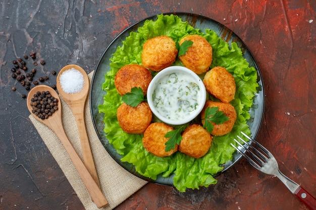 Vista superior nuggets de frango, garfo de alface no prato sal e pimenta-do-reino em colheres de madeira na mesa escura