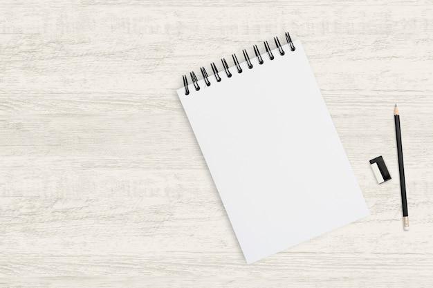 Vista superior objeto plano de fundo do caderno em branco e lápis na textura de madeira.