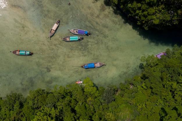 Vista superior ou aérea de barcos longtail flutuando na lagoa de águas claras na ilha de kao kra bi, tailândia