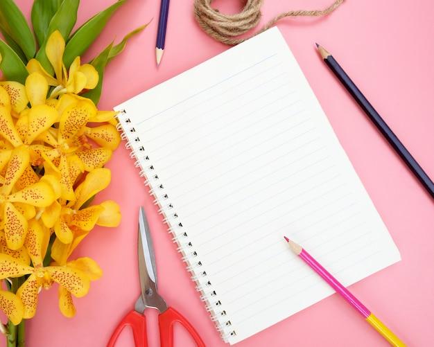 Vista superior ou configuração lisa do papel aberto do caderno, flores amarelas da orquídea, lápis da cor, tesouras e corda da natureza no fundo cor-de-rosa.