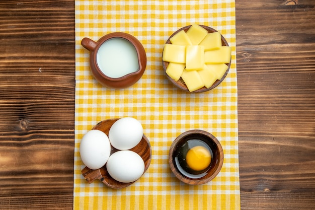 Vista superior ovos crus com fatias de queijo e leite na superfície de madeira produto ovos massa refeição alimentos crus