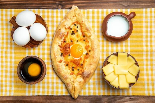 Vista superior ovos crus com fatias de queijo, ovo, pão e leite na superfície de madeira.