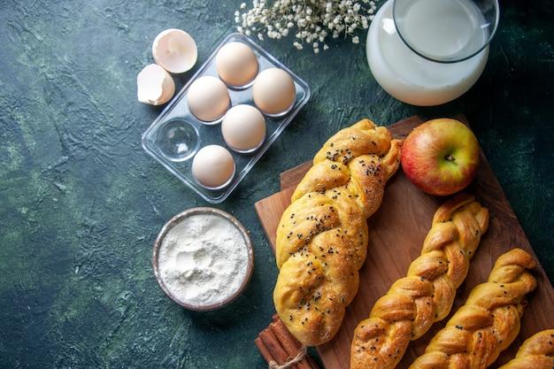 Vista superior ovos de galinha frescos com massa e leite em uma superfície escura pão comida refeição café da manhã leite escuridão cor de pássaro