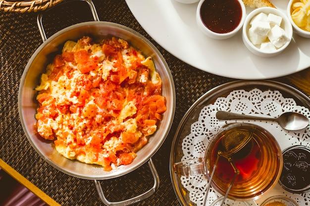 Vista superior ovos mexidos com tomate em uma panela e uma xícara de chá com geléia