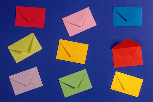 Vista superior para envelopes coloridos exibidos na vista superior do plano de fundo azul