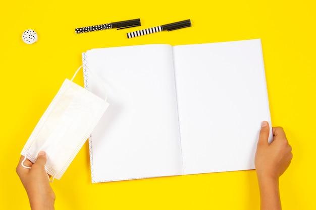 Vista superior para mãos de criança segurando uma máscara protetora médica, caderno aberto sobre fundo amarelo.