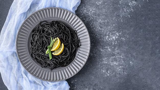 Vista superior pasta preta com choco de tinta e rodelas de limão em prato cinza