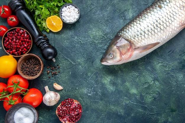 Vista superior peixe cru moedor de pimenta tomates alho verdes romã especiarias diferentes em pequenas tigelas na mesa