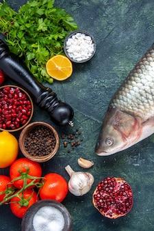 Vista superior peixe cru moedor de pimenta tomates alho verdes romã na mesa