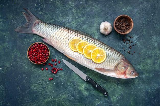Vista superior peixe cru, pimenta preta, sementes de romã em tigelas, faca de alho na mesa