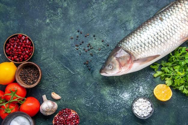 Vista superior peixe cru, tomate, alho, romã, temperos diferentes em pequenas tigelas no espaço livre da mesa