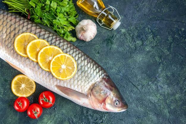Vista superior peixe cru, tomate, fatias de limão, garrafa de óleo no espaço livre da mesa