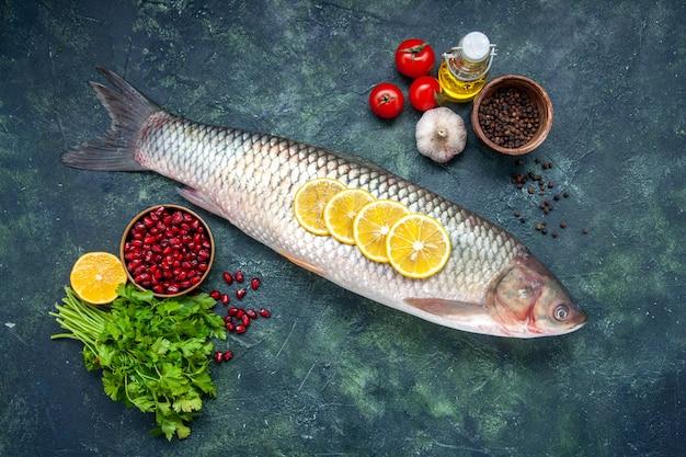 Vista superior peixe cru, tomate, fatias de limão, garrafa de óleo, verduras, mesa, espaço livre