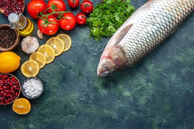 Vista superior, peixe cru, tomate, fatias de limão, sal marinho, em uma tigela pequena na mesa da cozinha com local de cópia