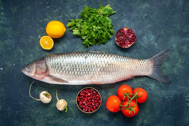 Vista superior peixe cru, tomate, rabanete, salsa, romã em uma tigela pequena com limão na mesa da cozinha