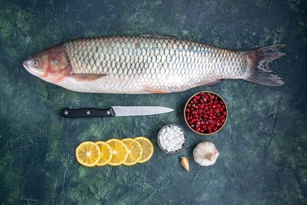 Vista superior peixe fresco fatias de limão faca tigela de sementes de romã na mesa da cozinha