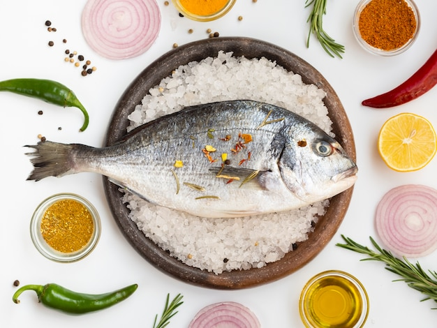Vista superior peixe fresco rodeado por condimentos