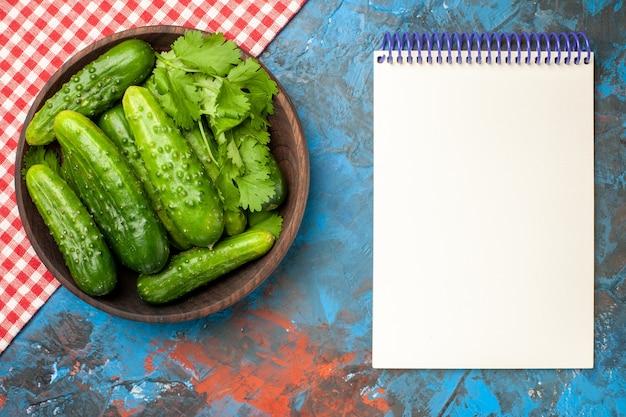 Vista superior pepinos frescos dentro do prato com o bloco de notas no fundo azul foto da saúde refeição madura cor salada comida dieta
