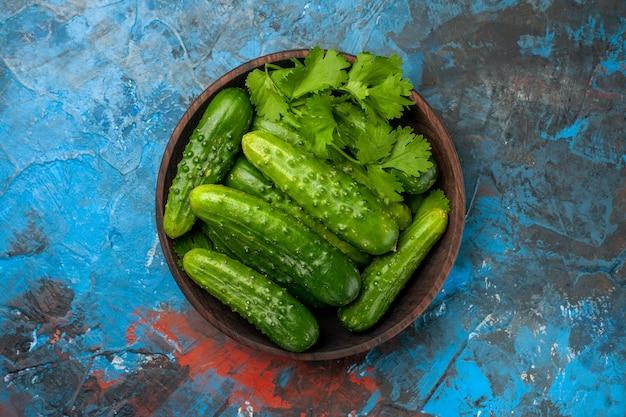 Vista superior pepinos frescos dentro do prato no fundo azul cor da foto salada madura comida refeição