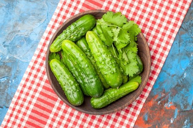 Vista superior pepinos frescos dentro do prato no fundo azul saúde foto refeição madura cor salada comida dieta
