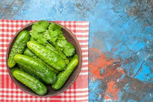 Vista superior pepinos verdes frescos dentro do prato em fundo azul