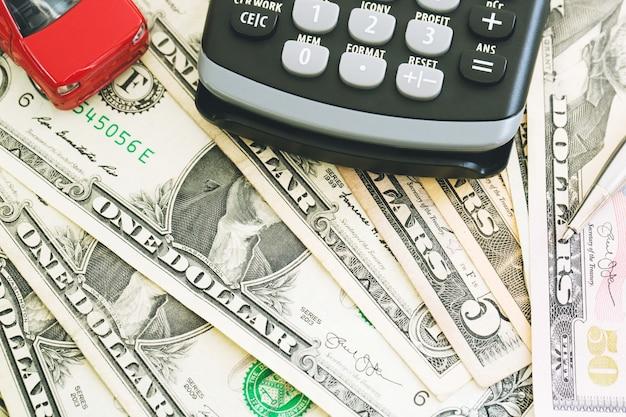 Vista superior pequeno carro vermelho sobre um monte de notas de dólar e euro, cálculo de custo