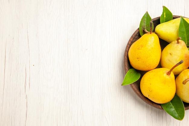 Vista superior peras frescas maduras frutas doces dentro do prato na mesa branca frutas amarelas frescas doces maduras