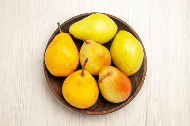 Vista superior peras frescas maduras frutas doces dentro do prato na mesa branca frutas amarelas frescas maduras doce