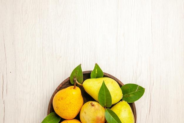 Vista superior peras frescas maduras frutas doces dentro do prato na mesa frutas amarelas frescas doce cor madura