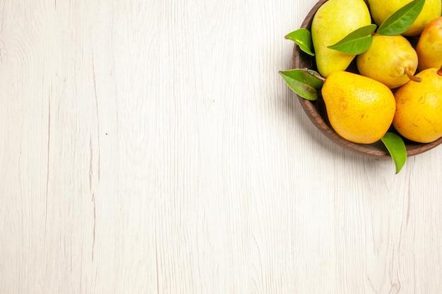 Vista superior peras frescas maduras frutas doces dentro do prato no fundo branco frutas amarelas frescas doces maduras