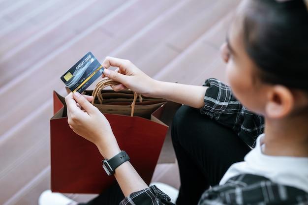 Vista superior, perto da mão de uma jovem segurando o cartão de crédito na mão com a sacola de compras