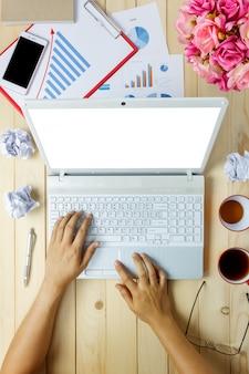Vista superior pessoa comercial discutindo gráficos e gráficos com laptop também caderno, café preto, flor, estacionário, caneta, calculadora no fundo da mesa de escritório.