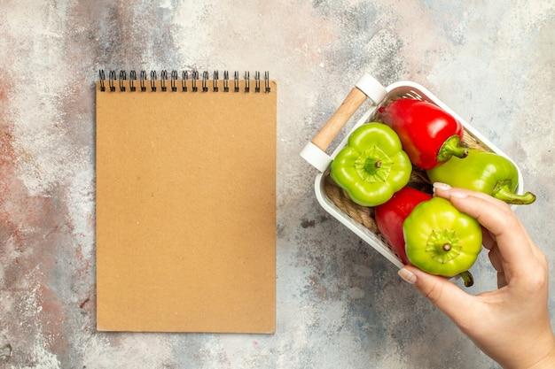 Vista superior pimentão verde e vermelho em cesta de plástico pimentão verde na mão feminina um caderno na superfície nua