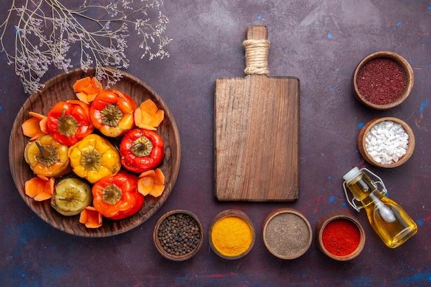 Vista superior pimentões cozidos com carne moída e diferentes temperos na superfície escura.