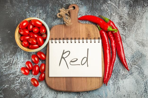 Vista superior pimentos vermelhos picantes com tomates frescos na foto de fundo escuro com alimentos maduros