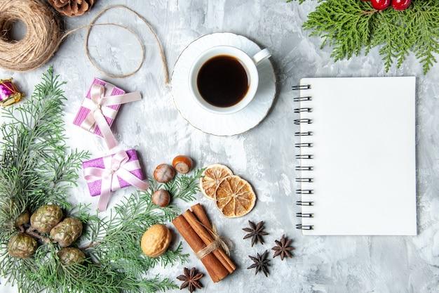 Vista superior pinheiro galhos paus de canela fio de palha caderno xícara de chá no fundo cinza