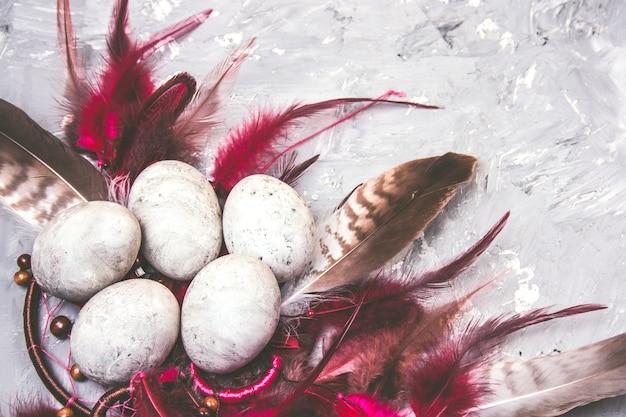 Vista superior pintada ovos de páscoa com efeito de pedra e penas brilhantes