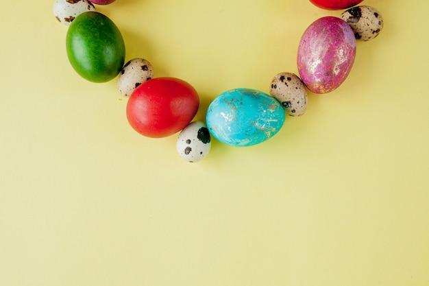 Vista superior pintado ovos frame de páscoa em forma de círculo sobre um fundo amarelo. copie o espaço