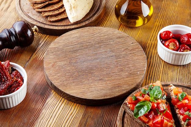 Vista superior placa de corte vazia para pizza ou carne. branches para servir comida em composição com tomates secos ao sol, bruschetta e utensílios em fundo de madeira. configuração plana