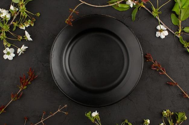 Vista superior placa preta vazia, juntamente com flores brancas no chão escuro