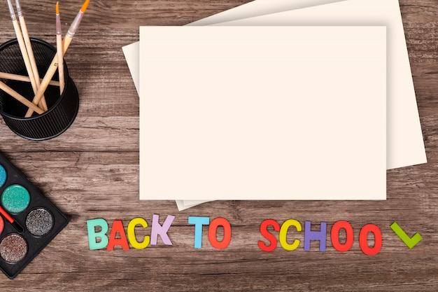 Vista superior plana colocar as mãos do menino tocar o alfabeto de volta à escola em fundo de madeira com espaço de cópia