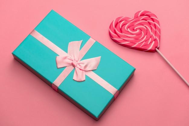 Vista superior plana colocar caixa de presente e caramelo em forma de coração no palito