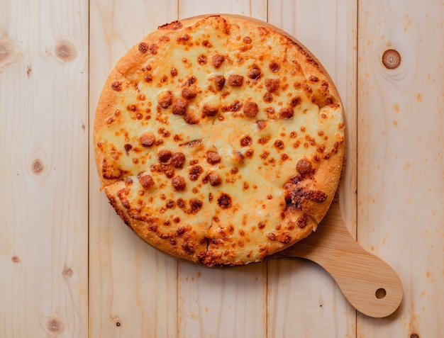 Vista superior plana da pizza pronta para comer em uma bandeja de madeira.