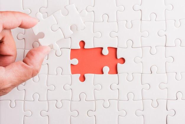 Vista superior plana da última peça do jogo de quebra-cabeça de papel branco segurando as últimas peças colocadas no lugar para resolver o problema missão completa