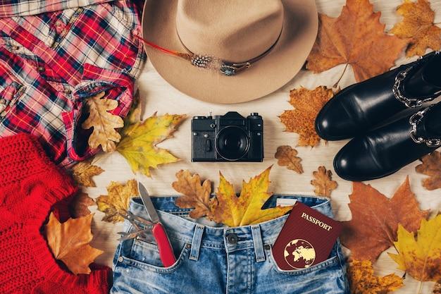 Vista superior plana de acessórios de estilo feminino, suéter vermelho, camisa de flanela quadriculada, jeans, botas de couro preto, tendência da moda outono, câmera fotográfica vintage, faca suíça, passaporte, roupa de viajante