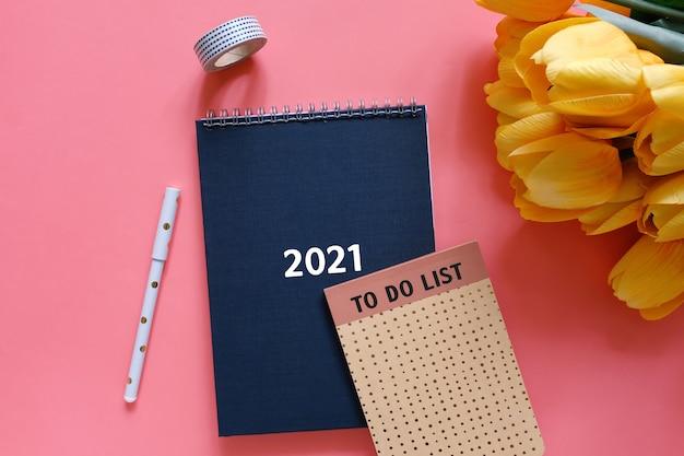 Vista superior plana do diário preto ou planejador 2021 com lista de tarefas e artigos de papelaria com flor de tulipa amarela em fundo vermelho, conceito de resoluções de ano novo
